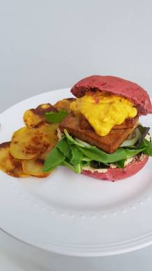 Tofu burger with hummus, cheese sauce and baked potatoes